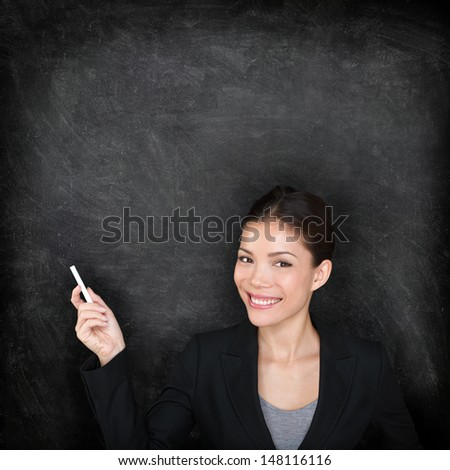 Teacher woman. Female teaching or college university student at blackboard in business suit. Young female mixed race Asian Caucasian female student. - stock photo