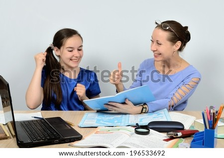 Teacher woman praises girl schoolgirl per job well executed - stock photo