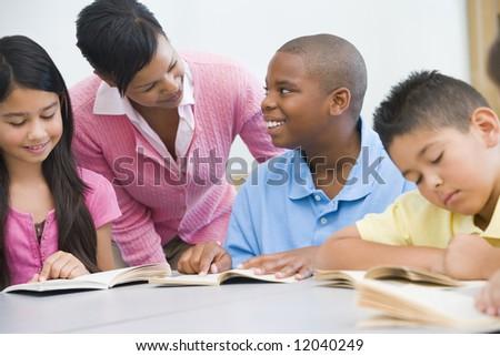 Teacher working with elementary school reading group - stock photo