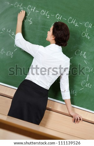 Teacher writes formulas with chalk at the blackboard