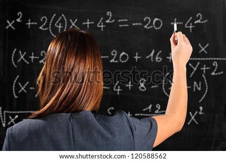 Teacher writing formulas on a blackboard - stock photo