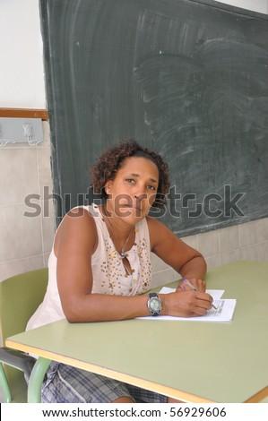 Teachers Aid Sitting at Desk - stock photo