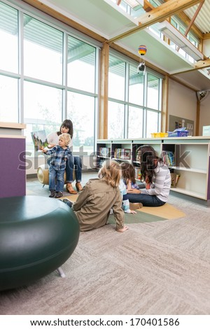 Teachers and primary students in school library - stock photo