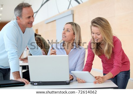 Teachers and teenage girl in front of computer