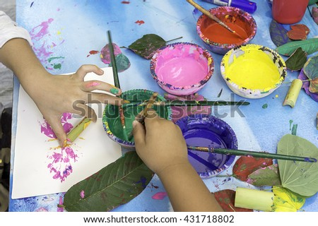 Teaching and training children paint roller. And color on paper, leaves, and teaching children to learn painting - stock photo