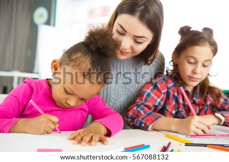 Teaching kids. Attractive cheerful young female teacher smiling watching her young student doing assignment on the lesson school classroom teaching learning education happiness childhood concept