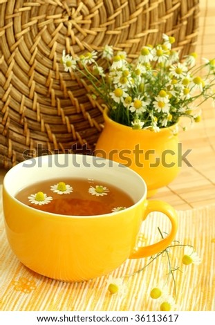 Teacup and  teapot with soothing herbal camomile tea. - stock photo