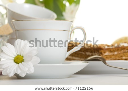 Teacup with flower on table - stock photo