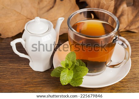 Teacup with fresh green tea with leaves in background - stock photo