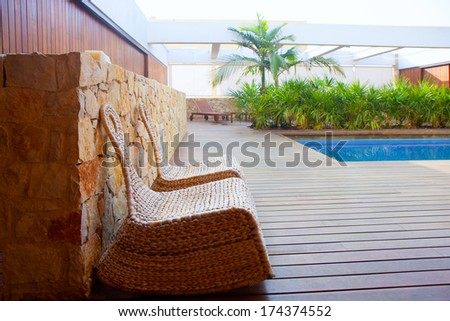 Teak wood modern house outdoor with swing chairs and palm trees pool - stock photo