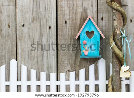 Teal blue birdhouse hanging over white picket fence and vine wrapped honey locust tree with wooden hearts - stock photo