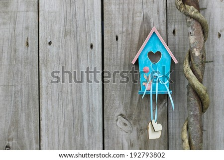 Teal blue birdhouse with wooden hearts next to vine wrapped honey locust tree - stock photo