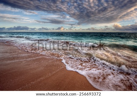 Teal waves crashing onto sandy shore - stock photo