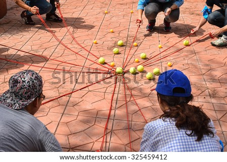 Team building activity, Tennis balls and table tennis balls with rope in harmonize activity - stock photo