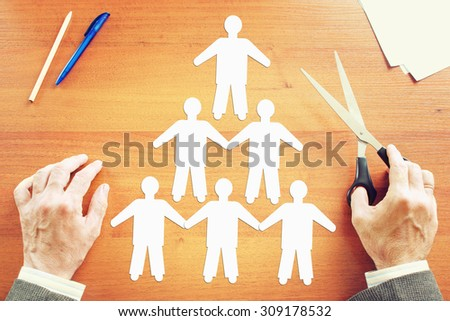 Team building concept. Abstract conceptual image with a man cutting human characters on the table - stock photo