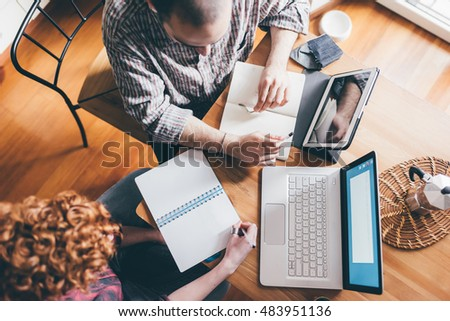 Team communication. Top view of two people discussing something using technological devices while sitting at the table - creativity, brainstorming, technology concept