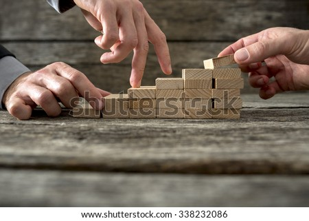 Team effort on the way to success - two male hands building stable steps with wooden pegs for the third one to walk his fingers up towards personal and career growth. - stock photo