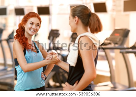 Team fitness. Beautiful fit women shaking hands at the gym. Teamwork and partnership concept