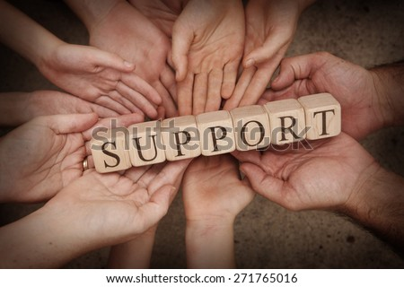 Team Holding Building Blocks Spelling out Support - stock photo