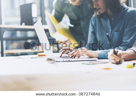 Team job. Photo young businessmans crew working with new startup project in modern loft. Generic design notebook on wood table. Horizontal, film effect - stock photo