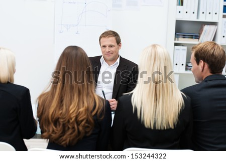 Team leader giving a motivational talk sitting across the table from his team of corporate business professionals - stock photo