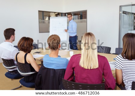 Team leader giving his business team a presentation as they sit around a conference table in the office, view from behind their seats