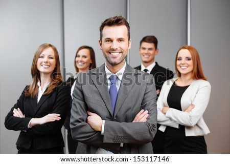 Team leader stands with coworkers in background - stock photo