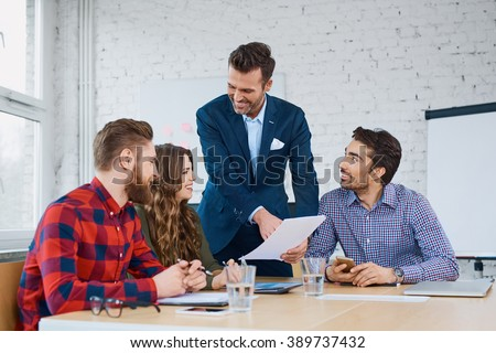 Team leader  talking with coworkers in modern office. Business or education concept