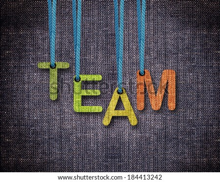 Team Letters hanging strings with blue sackcloth background. - stock photo