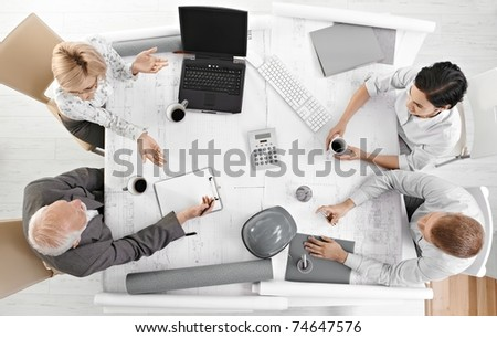 Team meeting from overhead view, businesspeople discussing work at office meeting table.? - stock photo