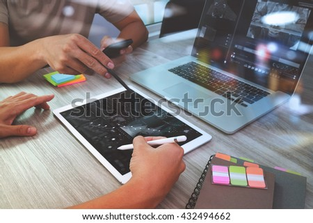 Team meeting. Hand businessman working with new startup project in modern office. Generic design notebook and digital table and smart phone on pale wood table. Horizontal, sun flare effect photo  - stock photo