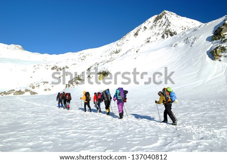Team of alpinists traversing Bucura Lake in National Park Retezat, Romania - stock photo