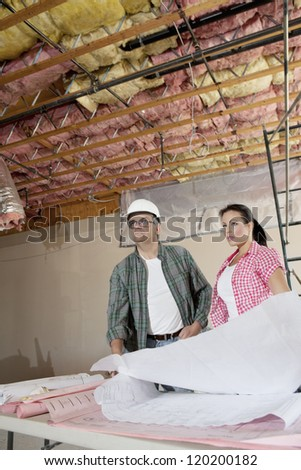 Team of architects looking away with blueprints at construction site - stock photo