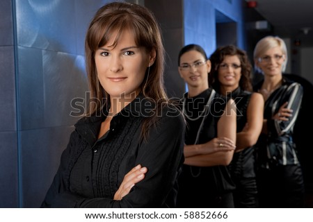 Team of attractive young businesswomen, waiting for lift in corporate ofiice lobby, smiling. - stock photo