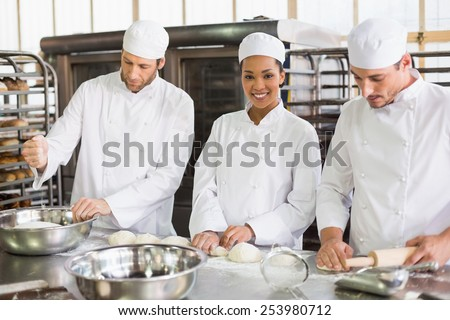 Team of bakers preparing dough in the kitchen of the bakery