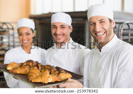 Team of bakers smiling at camera with trays of croissants in the kitchen of the bakery - stock photo