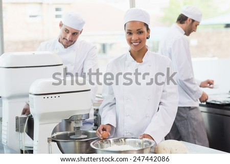 Team of bakers working at counter together in the kitchen of the bakery