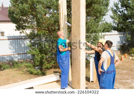 Team of builders erecting prefab wooden wall panels on the building site of a new house under construction - stock photo