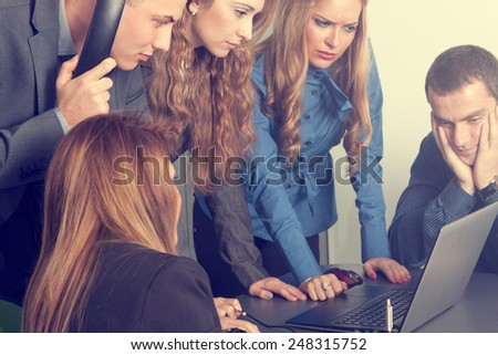 Team of business people anxiously watching computer and solving an important issue - stock photo