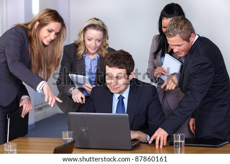 Team of 5 business people behind young businessman sitting and working on his laptop - stock photo