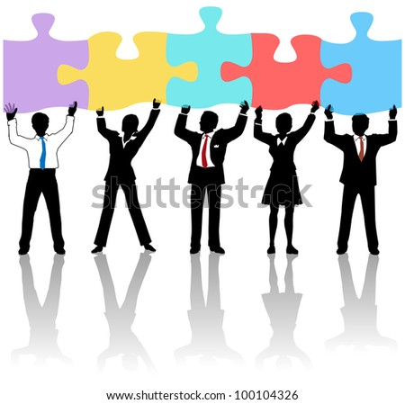 Team of business people collaborate holding up jigsaw puzzle pieces as a solution to a problem - stock photo