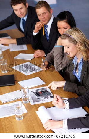 Team of 4 business people working on some calculations, calculator and documents on the conference table - stock photo