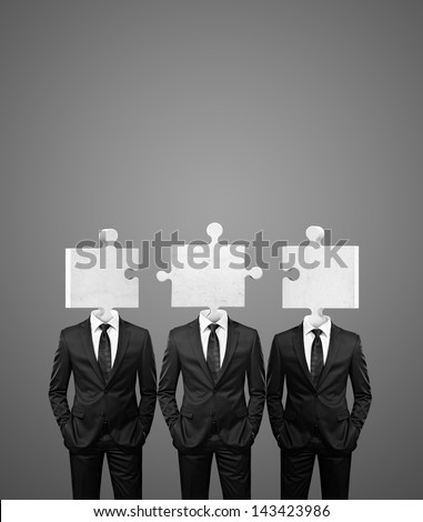 team of businessman with puzzle pieces instead heads - stock photo