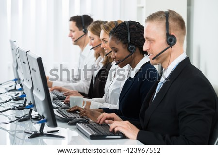 Team Of Businesspeople With Headsets Working In Call Center Office