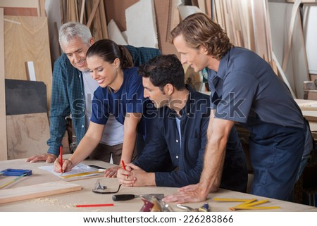 Team of carpenters working on blueprint at table in workshop - stock photo