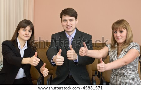 Team of cheerful businessmen show thumb up