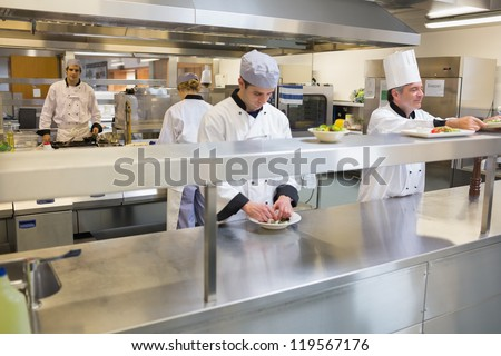 Team of Chef's at work in the kitchen - stock photo