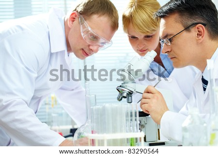 Team of chemists making experiments in laboratory - stock photo