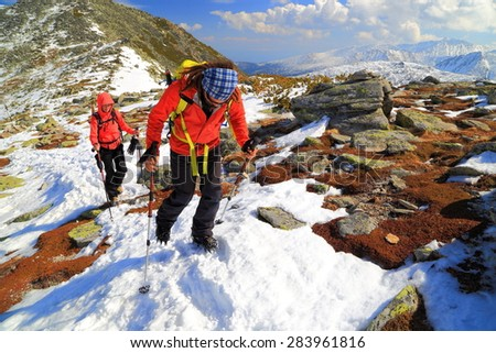 Team of climbers follow a snow covered route up on the mountain - stock photo