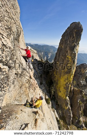 Team of climbers struggle for their next grip on a steep rock wall. - stock photo